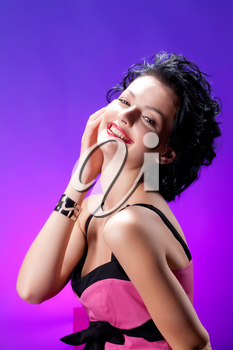 Young beautiful woman in fashinable dress on a studio background