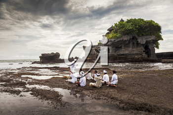 BALI, INDONESIA - APRIL 02: Balinese pilgrims at Tanah Lot temple on April -2, 2011, Tanah Lot, Bali. The temple has been part of Balinese mythology for centuries.