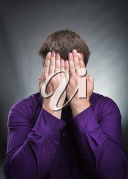 Man covers his face with hands over grey background