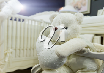 Baby bedroom with white teddy bear closeup