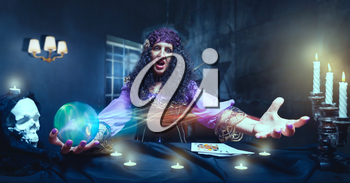 Angry sorceress working with crystal ball