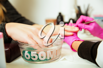 Manicure procedure with female hands in bowl of water. Professional manicure tool.