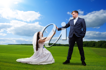Beautiful bride makes offer to the groom against the background of a green meadow