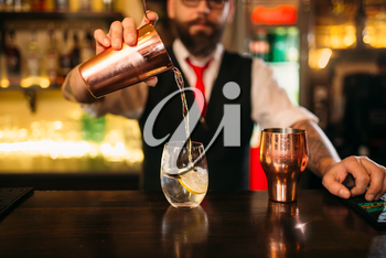 Bartender is making alcohol cocktail at bar counter. Barman with shaker