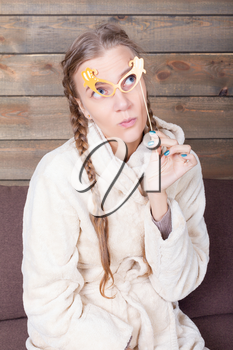 Young woman with yellow glasses on a stick, wooden background. Funny photo props. Fun accessories for shoots
