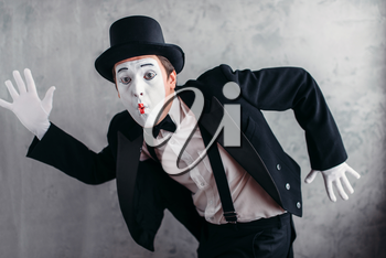 Pantomime theater artist posing, mimic male person with white makeup mask. Comedy actor in suit, gloves and hat