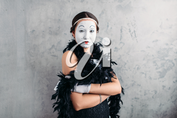 Pantomime actress with white makeup mask posing in studio. Comedy female artist performing