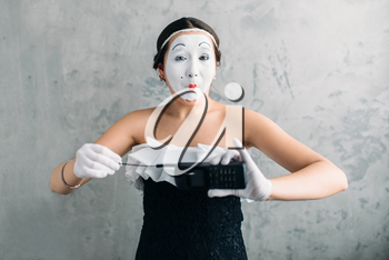 Mime female artist performing with mobile phone. Woman circus clown. Pantomime theater comedian with white makeup mask on face