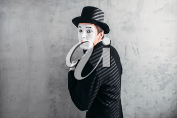 Male comedy artist posing, pantomime with white makeup mask. Circus actor in suit, gloves and hat