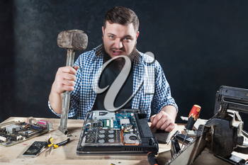Service engineer with hammer, laptop and electronic components on the desk. Engineering humor