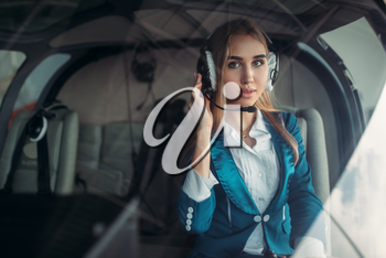 Female pilot in headphones poses in helicopter cabin, hangar interior on background, view from cabin. Air hostess in uniform sits in copter. Private airline