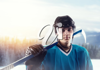 Portrait of ice hockey player in helmet and equipment, snowy forest on background. Ice-skating outdoors. Winter season men sport