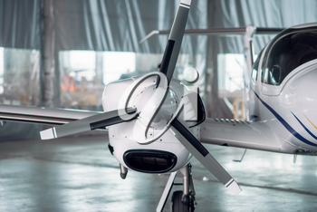 Lightweight propeller airplane in hangar, plane on inspection before flight. Private airline, air transportation