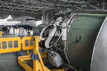 Jet airplane turbine on repairing in hangar, plane engine without covers on maintenance, nobody. Air transportation safety concept