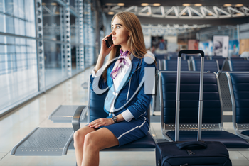 Stewardess with suitcase sitting on seat in waiting area in airport and talking by mobile phone. Air hostess with baggage, flight attendant with hand luggage, aviatransportations job