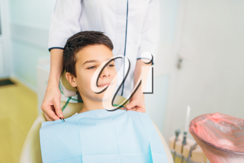 Boy in a dental chair, pediatric dentistry. The doctor examines the teeth of a small patient