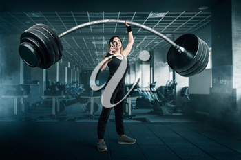 Female athlete with very big barbell talking by phone on workout in gim. Woman with weights, weightlifting sport concept