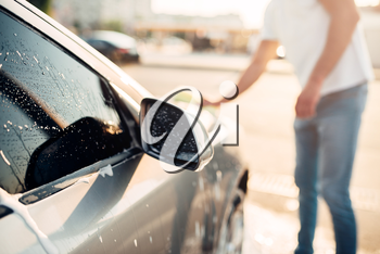 Male hand rubbing the car with foam, automobile in suds. Carwash station