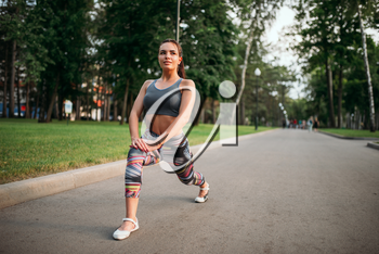 Athletic woman exercises, fitness training in park. Slim girl in sportswear, outdoor fit workout