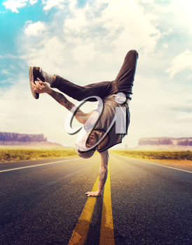 Young male hip hop dancer posing on a road. Modern urban dancing style