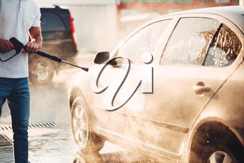 Male worker wash the car with high pressure washer. Car-wash station