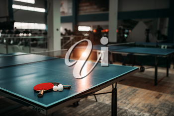 Ping pong table with rackets and balls in a sport hall, game equipment. Indoor tennis club