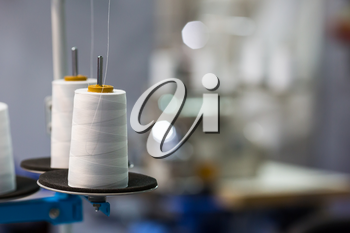 Spools of white threads on sewing machine, closeup. Cloth factory, weaving, textile production, clothing industry