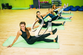 Athletic women in sportswear, workout on mat for fitness. Female sport teamwork in gym. Fit class, fitness exercise in motion