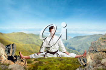 Martial arts karate master in white kimono and black belt doing extreme stretching exercise between the tops of the mountains