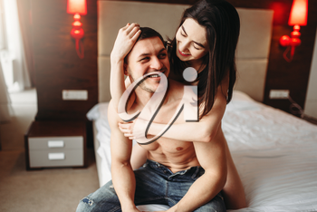 Happy love couple with naked body hugging on big white bed. Intimate games in bedroom, intimacy lovers