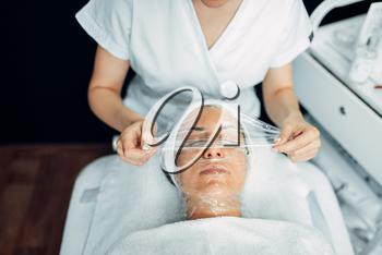 Doctor makes face mask, getting rid of wrinkles, cosmetology clinic. Facial skincare, rejuvenation procedure in spa salon, health care
