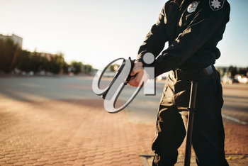 Male cop in uniform with gun in hands. Police officer with weapon. Law protection concept, safety control job