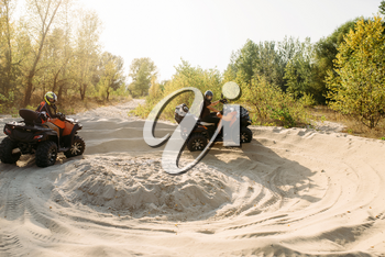 Two atv riders in helmets running laps on sand, offroad in forest. Riding on quad bike, extreme sport and travelling, quadbike adventure