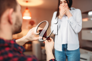 Young man makes an offer to get married to surprised woman and gives a ring. Modern apartment interior on background. Love couple relationship