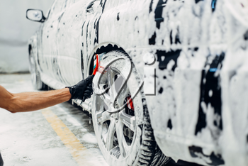 Carwash service, car in foam, side view. Auto detailing, washing of wheels with brush