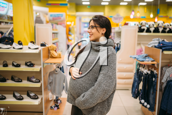 Future mother in the store for children and newborns, shoe department. Pregnant woman in shop of goods for infants