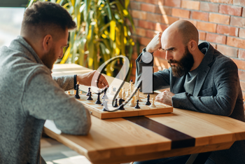 Male chess players playing at board, move the black elephant. Two chessplayers begin the intellectual tournament indoors. Chessboard on wooden table
