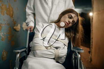 Male psychiatrist and crazy female patient in a wheelchair, mental hospital. Woman in straitjacket undergoing treatment in clinic for the mentally ill