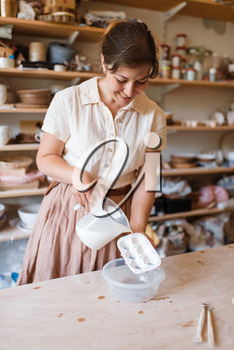 Female potter washes a foarm, pottery workshop. Woman cleans equipment after working. Handmade ceramic art, tableware from clay