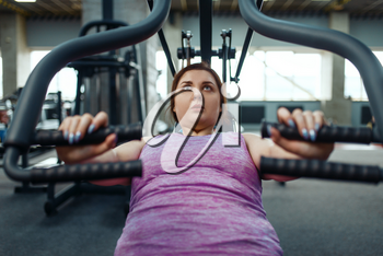 Overweight woman on exercise machine in gym, top view, active training. Female person struggles with excess weight, aerobic workout against obesity, sport club
