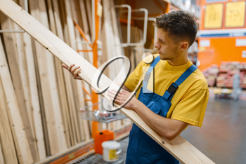 Male constructor choosing wooden boards in hardware store. Builder in uniform look at the goods in diy shop