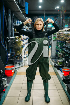 Fisherwoman in rubber jumpsuit in fishing shop, hooks and baubles on background. Equipment and tools for fish catching and hunting, accessory choice on showcase in store