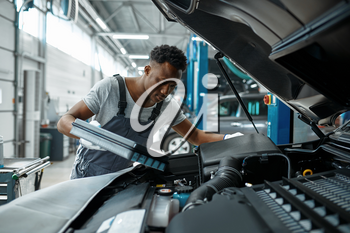 Male worker changes oil in engine, car service. Vehicle repairing garage, man in uniform, automobile station interior on background