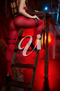 Sexy woman poses in red bdsm suit, back view, abandoned factory interior on background. Young girl in erotic underwear, sex fetish, sexual fantasy