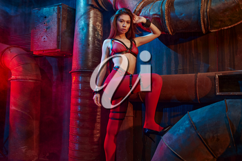Sexy woman poses in red bdsm stockings, abandoned factory interior on background. Young girl in erotic underwear, sex fetish, sexual fantasy