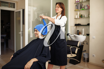 Hairdresser puts towel on woman's hair, front view, hairdressing salon. Stylist and client in hairsalon. Beauty business, professional service