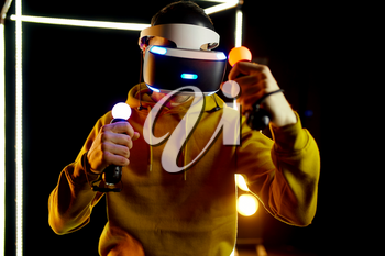 Young gamer plays in virtual reality headset and gamepad in luminous cube, front view. Dark playing club interior, spotlight on background, VR technology with 3D vision