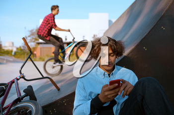 Bmx riders lifestyle, training in skatepark. Extreme bicycle sport, dangerous cycle exercise, street riding, teens biking in summer park