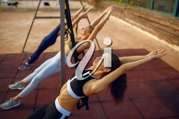 Women's with slim body doing fit exercise with ropes on sports ground, outdoors group training. Female athletes in sportswear, team fitness workout, teamwork