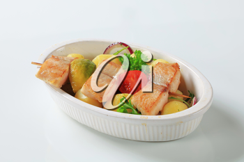 Fish skewer and potatoes in casserole dish